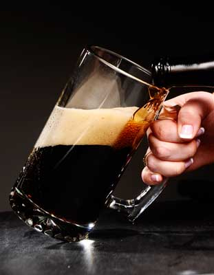 Dark Beer Pouring Into Mug